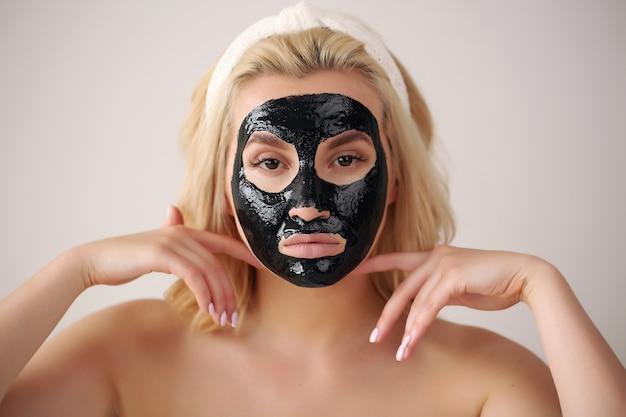 彼女の顔に黒いマスクを持つ女性