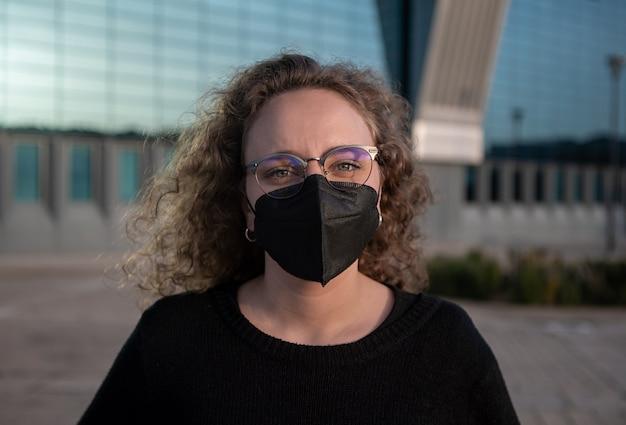 도시 공간에서 코로나 바이러스 또는 코로나 바이러스의 확산을 방지하기 위해 검은 마스크를 쓴 여성