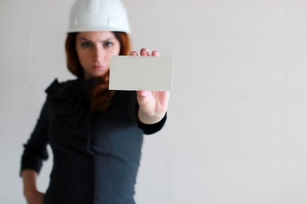 建設現場で彼の手に白紙のシートを持つ女性