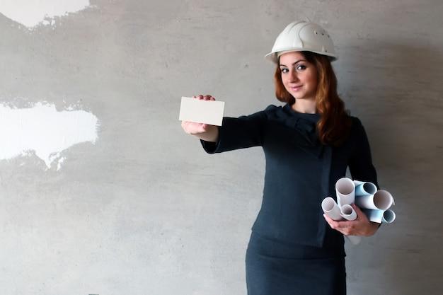 建設現場で手に白紙のシートを持つ女性