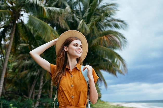 黄色のドレスと帽子の青いバックパックを持つ女性は、ヤシの木と砂に沿って海に沿って歩く