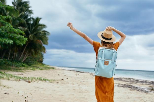 黄色のドレスと帽子に青いバックパックを持つ女性は、ヤシの木と砂に沿って歩く