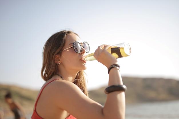 アクセサリーと飲み物のボトルを持つ女性