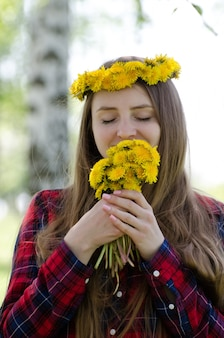 Женщина с букетом одуванчиков и венком на голове, наслаждаясь запахом