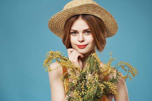 帽子をかぶった彼女の手にミモザの花束を持つ女性魅力的な外観の青い背景