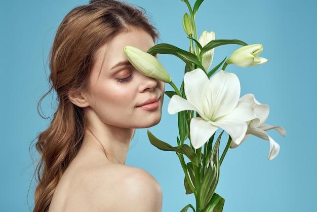 파란색 배경 알몸 어깨 아름다운 얼굴에 흰색 꽃의 꽃다발을 가진 여자