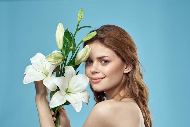 파란색 벌거 벗은 어깨 아름다운 얼굴에 흰색 꽃의 꽃다발을 가진 여자