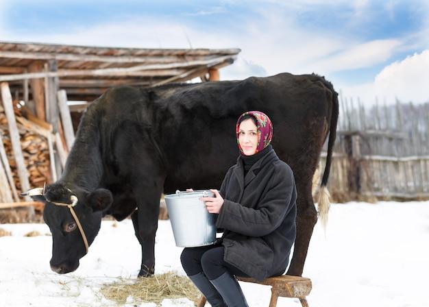 牛の近くで搾乳バケツを持つ女性