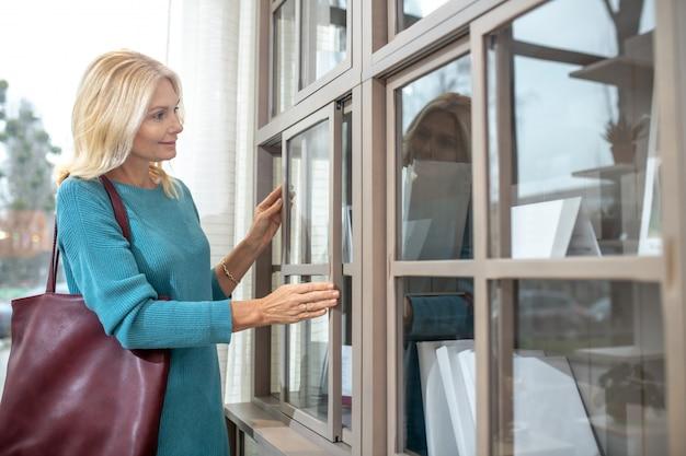 大きなガラス張りのワードローブの近くに立っている彼女の肩にバーガンディのバッグを持つ女性は、ガラスの近くに手を浮かべて笑っています。