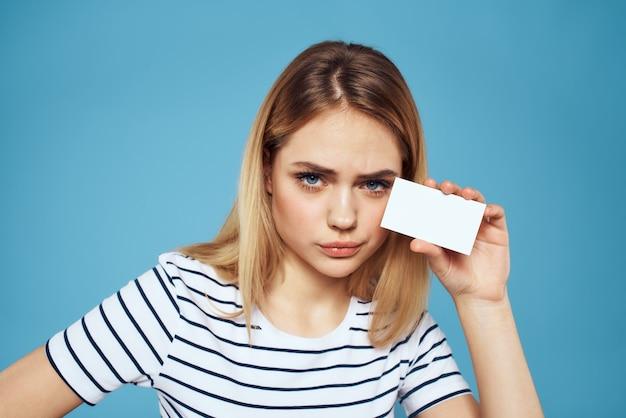 Женщина с визитной карточкой в руках полосатая футболка синий фон копией пространства.