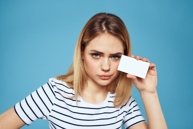 Женщина с визитной карточкой в руках полосатая футболка синяя стена copy space.