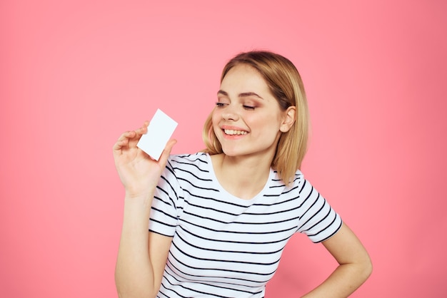 Женщина с визитной карточкой в руках полосатой футболке изолирована