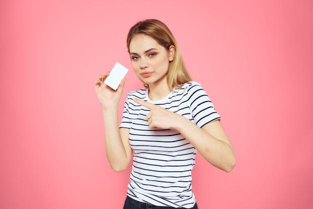 Женщина с визиткой в руках полосатую футболку розовую стену copy space реклама
