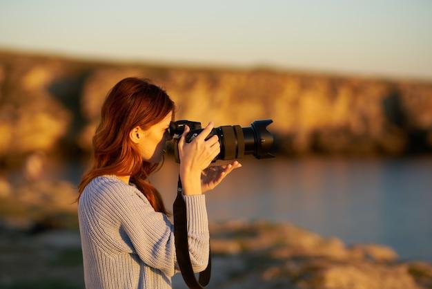 海の近くの自然の山の中で日没時にカメラを持つ女性。高品質の写真