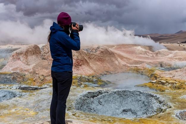 火山活動でいくつかの泥ピットを撮影するカメラを持つ女性