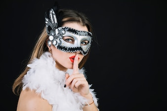 Woman with a carnival mask making silence gesture on black background