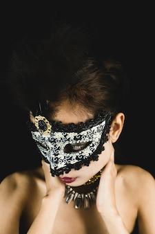 Женщина с маской карнавала на темном фоне