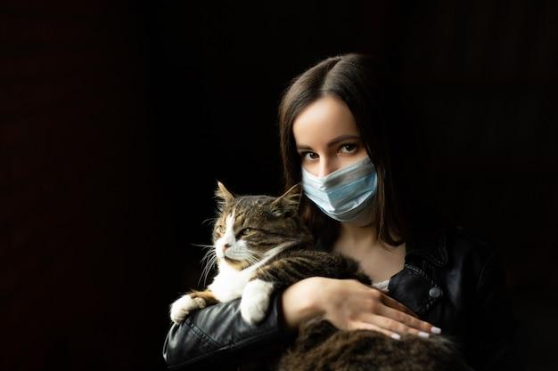 . 고양이와 여자, 건강 마스크를 쓰고, 코로나 바이러스 전염병