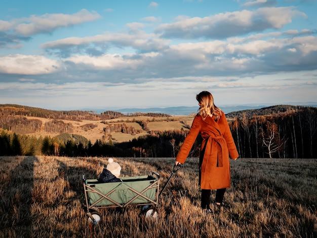 숲 속을 걷고 있는 마차에 아이를 안고 있는 여자