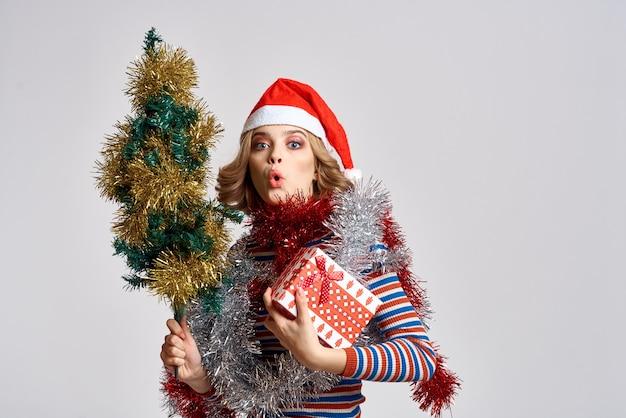 크리스마스 트리와 선물 모자 밝은 배경 모델 새 해를 가진 여자. 고품질 사진