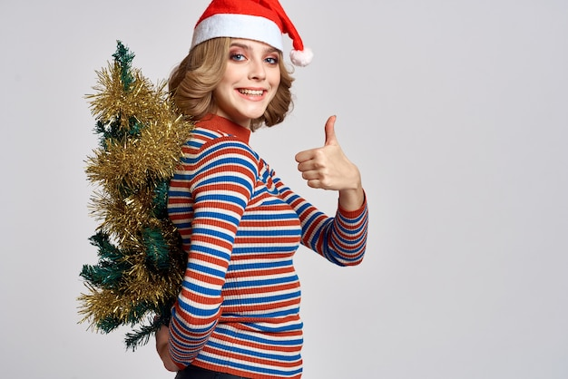 Женщина с елкой в руке желтая мишура праздники шапка подарки