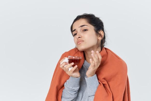 Женщина с простудой накрылась одеялом для лечения чая