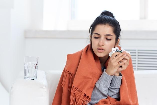 가정 치료에서 담요로 덮인 감기에 걸린 여자. 고품질 사진