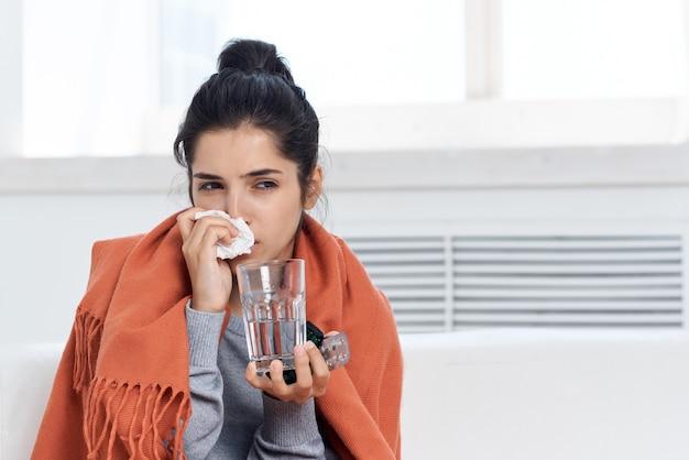 感染症を治療する錠剤と水の毛布ガラスで覆われた風邪の女性
