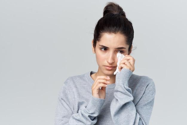 Женщина с простудой вытирает лицо инфекцией аллергии носового платка. фото высокого качества
