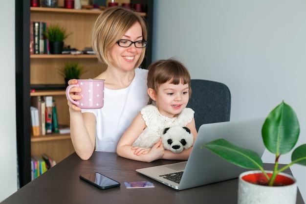 カップを持った女性と彼女の小さな娘が自宅のラップトップで何かを見ています