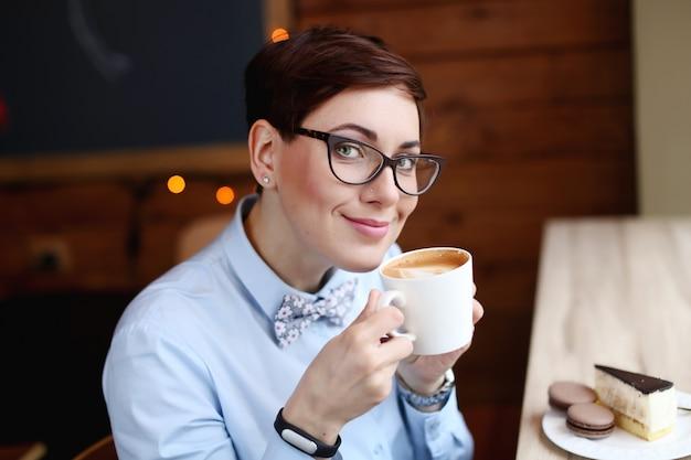 コーヒーを飲みながら、笑顔のコーヒーのカップを持つ女性