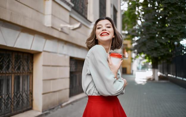 レンガ造りの建物と夏の化粧の赤いスカートの近くで彼女の手にコーヒーのカップを持つ女性。