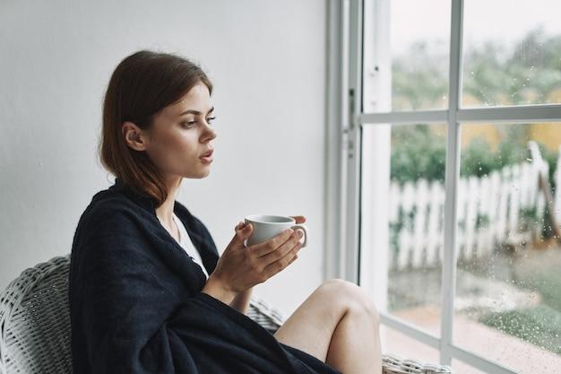 窓の近くで一杯のコーヒーを持っている女性は、屋内の肘掛け椅子に座っています