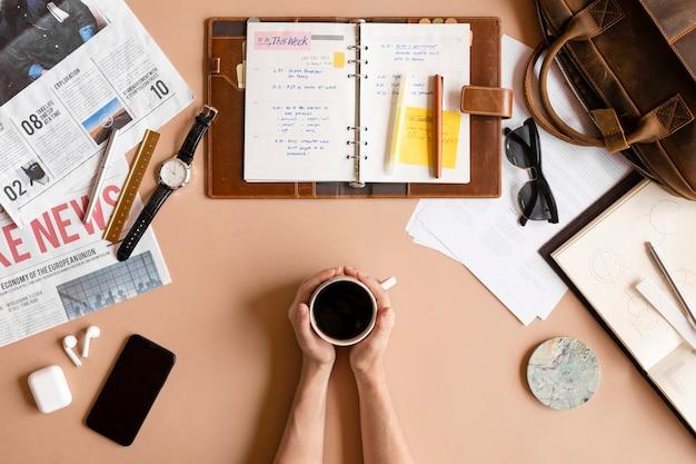 散らかった机の上に一杯のコーヒーを持つ女性