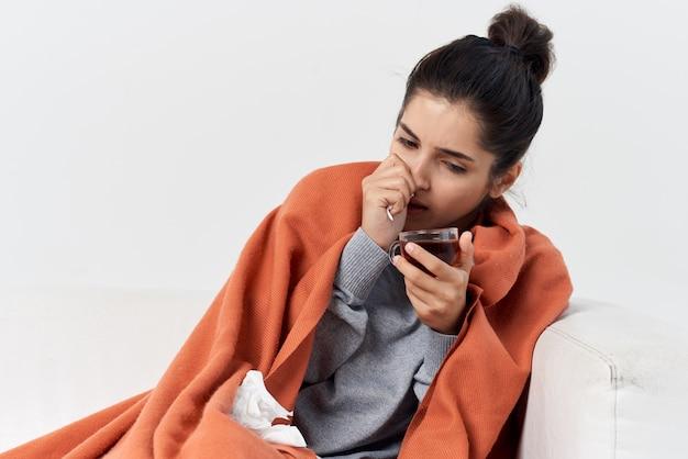 自宅の風邪の感染症で毛布の後ろに隠れているお茶のカップを持つ女性
