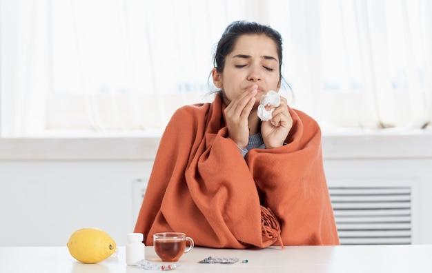 Женщина с чашкой чая, салфеткой в руке, проблемы со здоровьем, насморк, витамины.