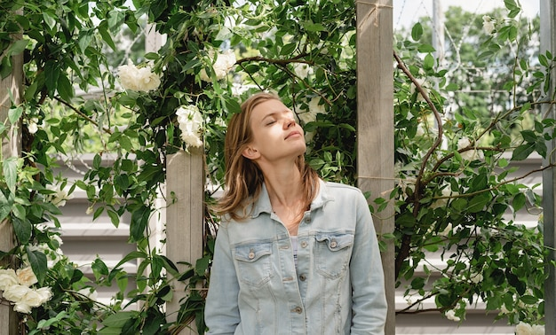 背景と自然光の白いバラの庭とデニムジャケットを持つ女性