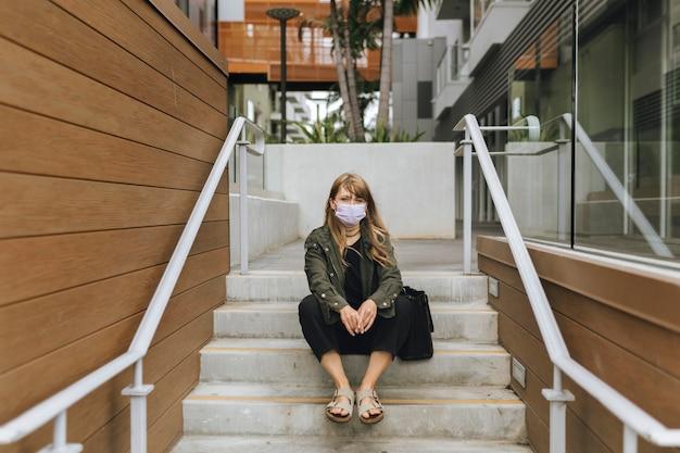 コロナウイルスの発生時に公共の場でフェイスマスクを持つ女性