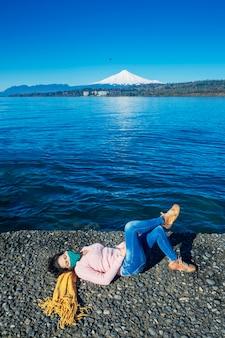 湖畔に横になっているフェイスマスクを持つ女性