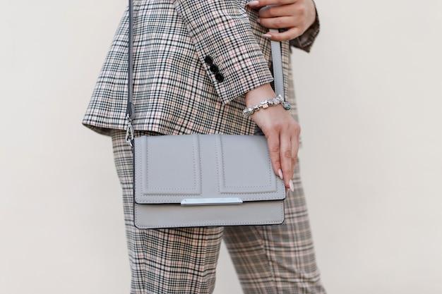 ファッショナブルなバッグとスタイリッシュな市松模様のスーツを持つ女性