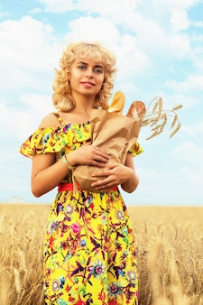 熟した小麦の畑でパンのフルパックを持つ女性