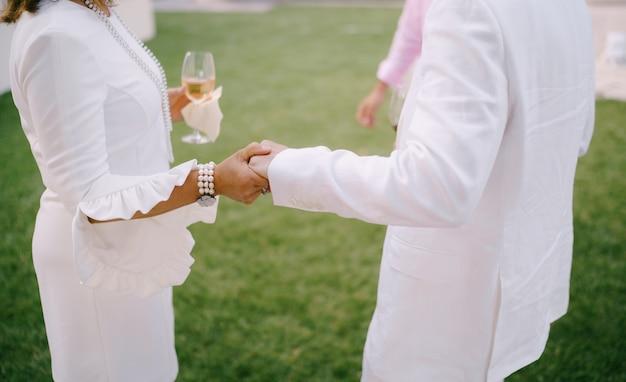 그녀의 손에 유리를 가진 여자는 녹색 잔디에 서 있는 동안 남자 손을 잡고