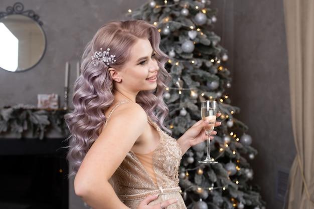 クリスマスツリーの近くにシャンパングラスを持った女性。新年のコンセプト。