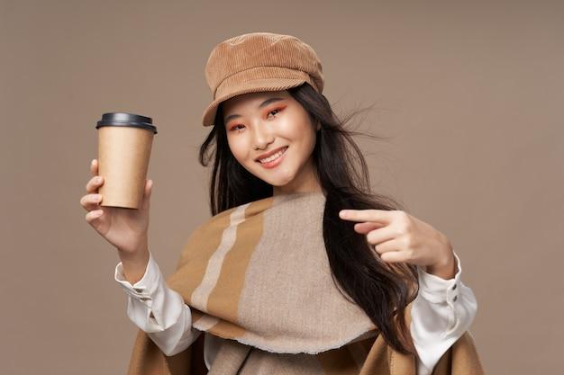 Женщина с бокалом кофе согревающего напитка элегантный стиль улыбка яркий макияж очарование модели