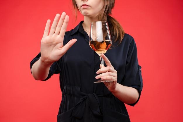 一時停止の標識でワインのジェスチャーの手のガラスを持つ女性
