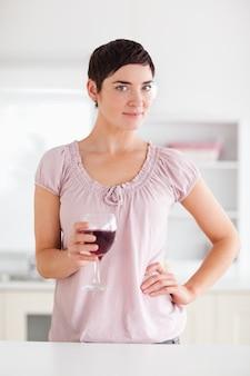 카메라를보고 와인 한 잔을 가진 여자