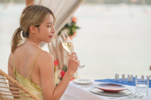 グラスワインを持った女性、海の近くで日没時にロマンチックなディナー。