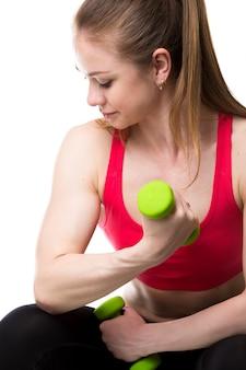 緑のダンベルを持つ女性