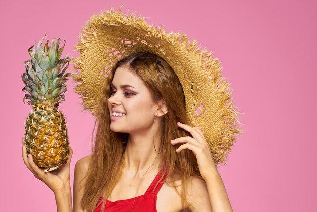 麦わら帽子の手に銃を持った女性明るいメイクエキゾチックなフルーツ夏ピンク。