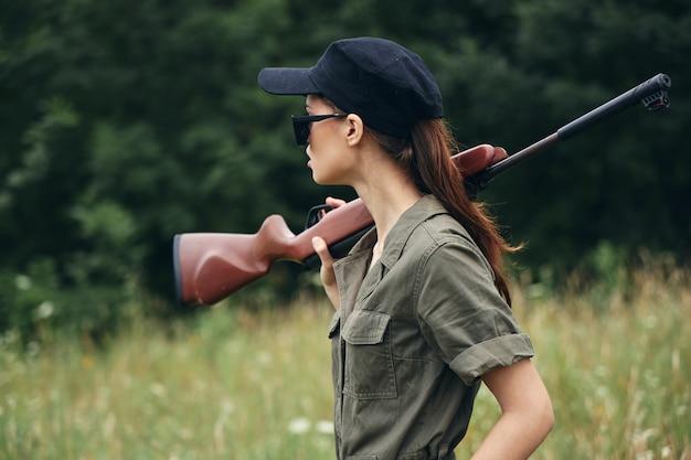 森と緑の草の木の屋外で銃を持つ女性